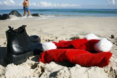 Santa relaxing on Boxing Day. Father Christmas on Boxing Day relaxing strolling on the beach after the busiest night of the year, showing his hat, clothes and stock photography