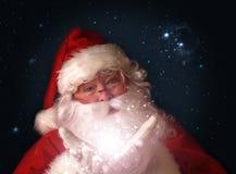 Santa retenant les lumières de Noël magiques dans des mains Photographie stock libre de droits