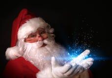 Santa retenant les lumières magiques dans des mains Images libres de droits