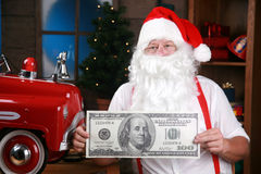 Santa retient des cents billets d'un dollar géant Photo stock