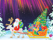 Santa rides on Reindeer dragging the sledge Royalty Free Stock Image