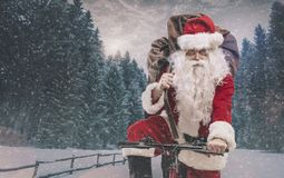 Santa riding a bicycle and carrying gifts. Santa Claus riding a bicycle and carrying a heavy sack with gifts for Christmas under the snow stock photography