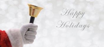 Santa Ringing une cloche d'or au-dessus d'un fond argenté de bokeh avec du Sn photo stock