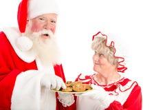 Santa rit et prend le biscuit Images stock