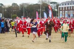 Santa Run på den Weymouth stranden som har gyckel arkivbilder