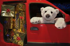 Santa's assistant. Teddy bear delivering golden packages in a red van Stock Photos