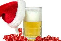 Santa's Beer. Santa's hat hanging on a beer mug royalty free stock images