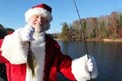 Santa's Big Catch. On a last break before the seasonal rush Santa has been fishing and caught this little one stock images