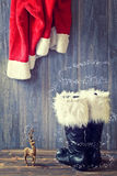 Santa's Boots. Santa's black boots with fur trim and hanging jacket Royalty Free Stock Photo