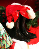 Santa's Boots and Hat. Santa's boots with his hat draped over them &  fir branch behind Royalty Free Stock Image