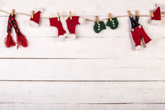 Santa`s clothes. In a cloth line with cloth pins, over a wood white background Royalty Free Stock Photo