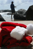 Santa's day off. Father Christmas on Boxing Day relaxing fishing after the busiest night of the year, showing his hat, clothes and the ocean in the background royalty free stock images