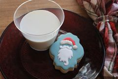 Santa`s milk and sugar cookie on wooden board near plaid napkin royalty free stock photos