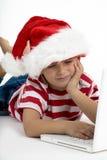 Santa's elve placing order on laptop Stock Image