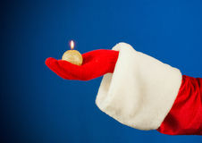 Santa's hand holding a burning candle Royalty Free Stock Photo