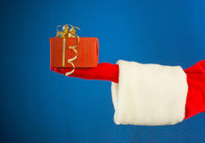 Santa's hand holding a present Royalty Free Stock Images