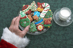 Santa's Hand Taking Homemade Decorated Cutout Christmas Cookies Stock Photos