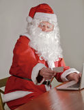 Santa s Hands holding a credit card and using laptop computer for online shopping Royalty Free Stock Photo