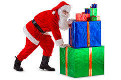 Santa's hard work. Santa Claus is pushing a lot of gifts. Isolated on white background Royalty Free Stock Photography