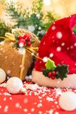 Santa`s hat with Christmas ornaments and falling snow, on red fabric. Royalty Free Stock Images