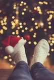 Santa`s hat. Detail of woman`s feet wearing warm winter socks and small Santa`s hat, placed on the table with Christmas tree and Christmas lights in background Stock Image