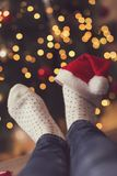 Santa`s hat. Detail of woman`s feet wearing warm winter socks and small Santa`s hat, placed on the table with nicely decorated Christmas tree and Christmas Royalty Free Stock Images
