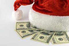 Santa`s hat and dollars. Santa`s hat and four 100 dollar bills Royalty Free Stock Images