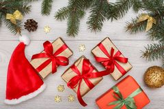 Santa`s hat, gift boxes, fir tree branches with cones and christmas toys stock photography