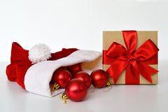 Santa's hat, red baubles and Christmas gift Stock Photography