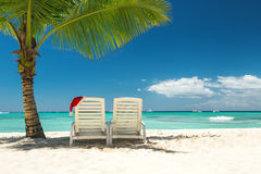 Santas hat and sun loungers on the tropical beach stock photo