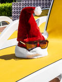 Santa's hat with sunglasses on a lounger by the pool on a tropic Royalty Free Stock Images