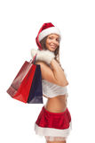 Santa`s  helper. Beautiful sexy girl wearing santa claus clothes with paper gift bags in hands Royalty Free Stock Photos