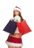 Santa`s  helper. Beautiful sexy girl wearing santa claus clothes with paper gift bags in hands Stock Photography