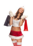 Santa`s helper. Beautiful sexy girl wearing santa claus clothes with paper gift bags in hands Stock Image
