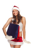 Santa`s  helper. Beautiful sexy girl wearing santa claus clothes with paper gift bags in hands Stock Images