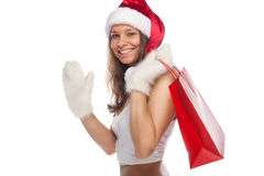 Santa`s  helper. Beautiful sexy girl wearing santa claus clothes with paper gift bags in hands Royalty Free Stock Photo
