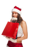 Santa`s  helper. Beautiful sexy girl wearing santa claus clothes with paper gift bags in hands Royalty Free Stock Photography