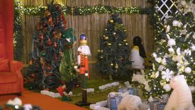 Santa`s helper or elf sits on Santa`s chair, celebrates Christmas. Child rejoices in Christmas. Happy cute girl in elf. Costume plays in Christmas area stock video