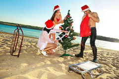 Santa's helper and Santa at the tropical beach Stock Image