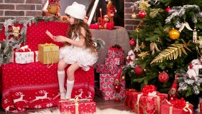 Santa`s helper sort the presents, wrapping gifts, little girl lays out the name cards on Christmas gifts, the girl stock video