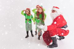 Santa`s helpers working at North Pole. He Reading wishes list. Santa`s helpers are working at North Pole, elves and kids holding gift boxes. Merry Christmas Stock Photo