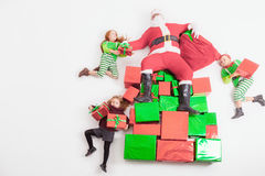 Santa`s helpers working at North Pole. He reading wishes list. Santa`s helpers are working at North Pole, elves and kids holding gift boxes. Merry Christmas Royalty Free Stock Photos