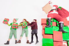 Santa's helpers working at North Pole. He Reading wishes list. 's helpers are working at North Pole, elves and kids holding gift boxes. Merry .  sitting at many Royalty Free Stock Image