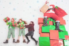 Santa`s helpers working at North Pole. He Reading wishes list. Santa`s helpers are working at North Pole, elves and kids holding gift boxes. Merry Christmas Stock Image