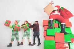 Santa& x27; s-hjälpredor som arbetar på nordpolen Honom som läser önskalistan Arkivbilder