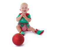 Santa's little helper. Little baby boy dressed in Elf costume, playing on the floor Royalty Free Stock Image