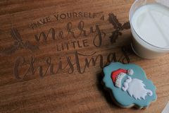 Santa`s milk and sugar cookie on Merry Little Christmas wooden board stock image