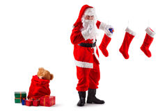 Santa's mission. Santa Claus stands and puts Christmas gifts in socks. Isolated on white Royalty Free Stock Photo