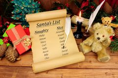 Santa`s Naughty And Nice List. On an old paper scroll with a festive background stock photo