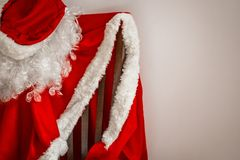 Carnival costume of Santa Claus. Santa`s outfit hangs on a chair. Help yourself, take a step towards your dream. Give your loved ones a New Year`s fairy tale Stock Photo